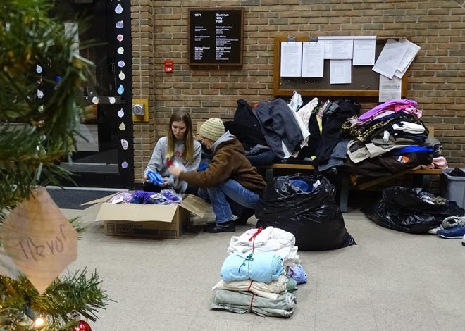 Savannah and Cheri Pennington, from left, prepare items for the Warm Winter Clothing Drive on Tuesday evening in the Bucyrus City Hall lobby.
