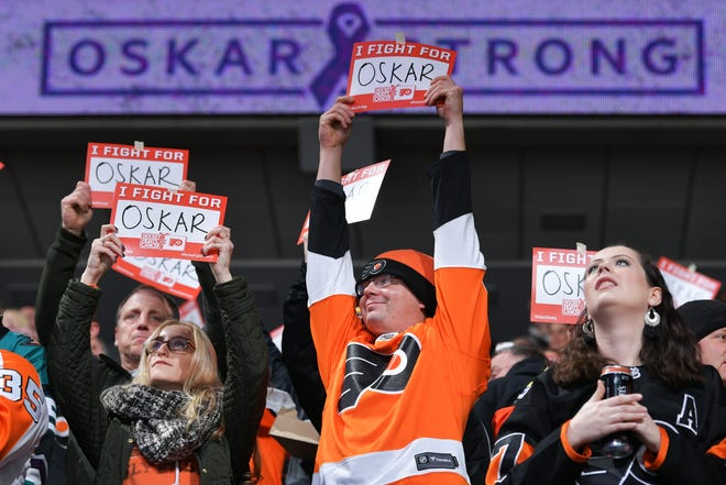 Fans hold up signs in support of Oskar Lindblom #23 of the Philadelphia Flyers who was recently diagnosed with Ewing's sarcoma, a rare form of bone cancer.