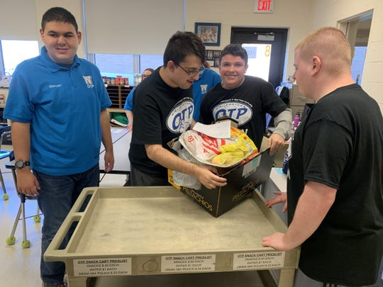 Students in Williamstown High School's Occupational Transitions Program load a meal kit on to a cart for delivery to a local family in need Dec. 18, 2019.