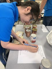 Cecelia, a student in Williamstown High's Occupational Transitions Program, checks off the list of items needed in a meal kit, Dec. 18, 2019.