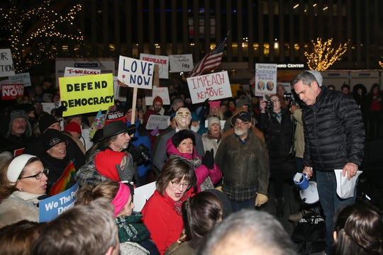 Mark Santangelo leads other activists as they gather to rally in support of the impeachment and removal of President Donald Trump, Tuesday, Dec. 17, 2019, at Fountain Square in Cincinnati.