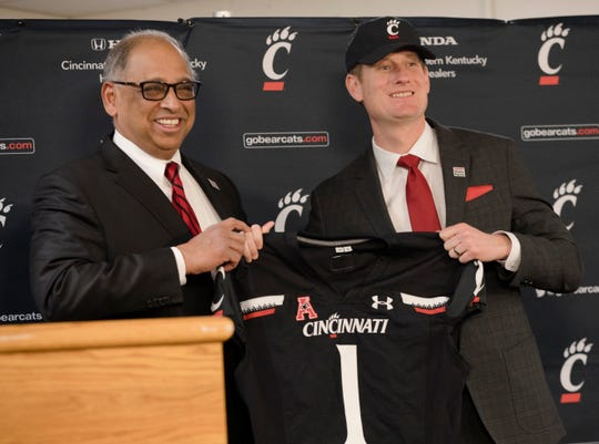 UC president Neville G. Pinto hands John Cunningham, UC Athletic director, a jersey during his first press conference as University of Cincinnati's Athletic Director on Wednesday, Dec. 18, 2019, at Fifth Third Arena at the University of Cincinnati in Cincinnati.