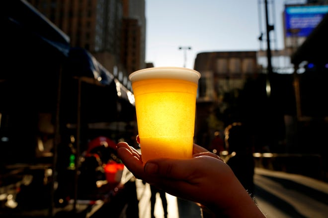 Becca Strayer, of Owensville, presents a cup of Fretboard's Bootsy 'Brewski' IPA during the Brewmania Tasting & Tunes event on Fountain Square in downtown Cincinnati on Wednesday, Oct. 2, 2019. Local breweries, bands and food trucks gathered on the square to raise money for charity.