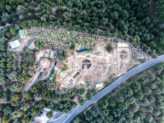 In this undated photo provided by the Greek Culture Ministry on Tuesday, Dec. 17, 2019, an aerial view is seen of two 3,500-year-old tombs, center and right, discovered near the southwestern Greek town of Pylos, together with one found decades ago, left. The ministry said American archaeologists have discovered two monumental royal tombs dating 3,500 years back, near a large Bronze Age palace that featured in Homer's Odyssey. Recovered grave goods included a golden seal ring and a golden Egyptian amulet. (Greek Culture Ministry via AP)