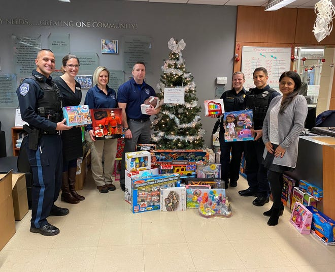 (Left to right) Officer Nick Dante; Somerset Hills YMCA Branch Executive Director Kim Cole; PBA Vice President Officer Tracy Baldassare; Cpl. Steve Mathews; Sgt. Peggy Corsentino; Officer Dominic Aboosamara; and Somerset Hills YMCA Financial Assistance Coordinator Beatriz Dominguez. The group is pictured in front of the Giving Tree at Somerset Hills YMCA with toys donated by PBA members and the community. Ray Gizienski, president of the PBA, also helps coordinate the toy drive for the Y.