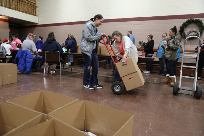 Ivy Michael, right, and Krista Maust load  a dolly while volunteering for the Salvation Army's distribution day on Wednesday. The charity helped 444 families with food and presents for the holidays.