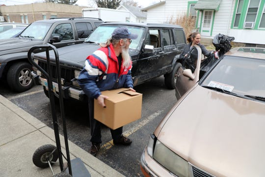 Jeff Young helps load Lisa Johnston's car after Johnstson's visit to the Salvation Army in Coshocton on Wednesday. The charity helped 444 local families enjoy a bright holiday season with food and presents.