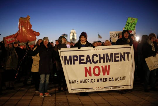Julia Williams of Des Moines holds an Impeachment Now banner as central Iowans gather outside of the state Capitol in Des Moines, Iowa, on Tuesday, Dec. 17, 2019, during a rally for the impeachment of President Donald Trump.