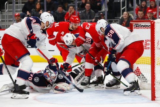 Columbus Blue Jackets defenseman David Savard (58) keeps the puck out of the net as goaltender Joonas Korpisalo is out of position against the Detroit Red Wings in the second period Tuesday, Dec. 17, 2019, in Detroit.