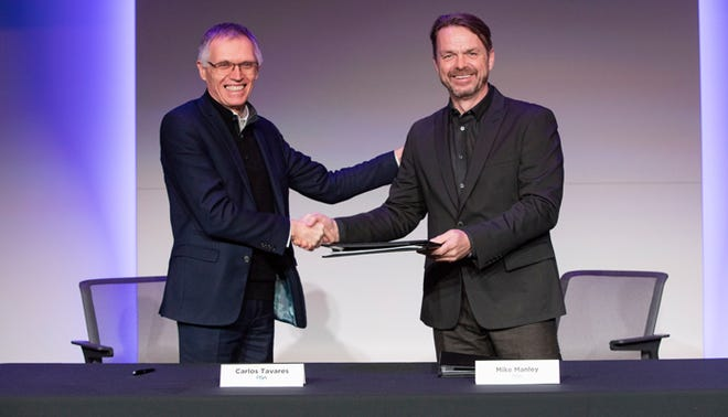 Carlos Tavares, chair and CEO of Peugeot-maker PSA Groupe, shakes hands with Fiat Chrysler Automobiles CEO Mike Manley to commemorate the signing of a binding agreement on a merger.