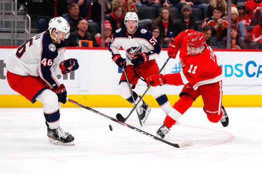 Detroit Red Wings right wing Filip Zadina takes a shot defended by Columbus Blue Jackets defenseman Dean Kukan in the second period at Little Caesars Arena, Tuesday, Dec. 17, 2019, in Detroit.