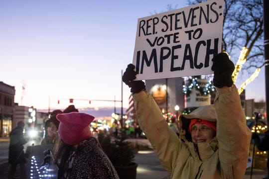 Cheryl Voglesong of Troy, right, holds a sign to ask Representative Haley Stevens's vote to impeachment President Trump during a rally near 9 Mile Road and Woodward Avenue in Ferndale, Tuesday, Dec. 17, 2019.