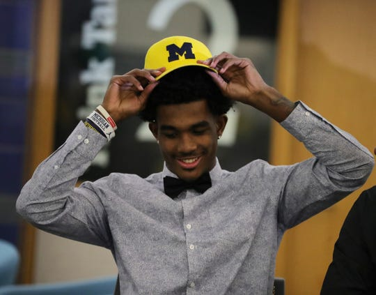 West Bloomfield senior Makari Paige puts on his hat after signing his letter of intent to play football at Michigan, Dec. 18, 2019 at West Bloomfield high school.