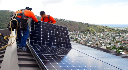 In this July 8, 2016, file photo, Radford Takashima, left, installer for RevoluSun, and lead installer Dane Hew Len, right, place solar panels on a roof in Honolulu. If you have the cash, most experts agree buying a solar system outright is a better investment than leasing or taking out a loan.