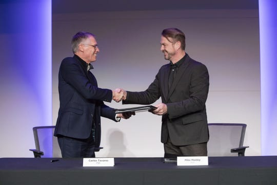 PSA CEO Carlos Tavares, left, and  Fiat Chrysler CEO Mike Manley shake hands on the merger of the automakers Wednesday.