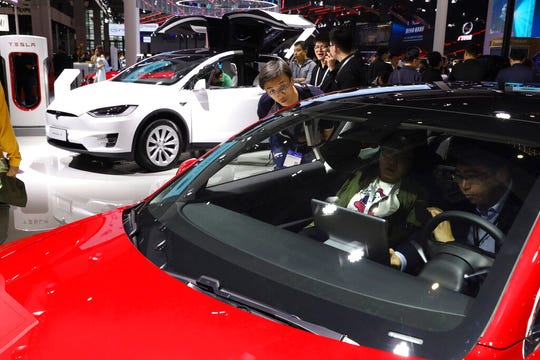 In this April 17, 2019, file photo, attendees take a look at electric cars from Tesla at the Auto Shanghai 2019 show in Shanghai.