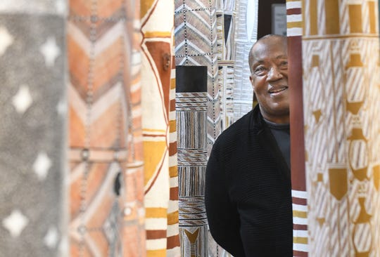 "Charles H. Wright Museum of African American History President and CEO Neil Barclay is seen among exquisitely crafted memorial poles created by Aboriginal artists from Australia in an exhibit 'The Inside World,"" Dec. 17, 2019."
