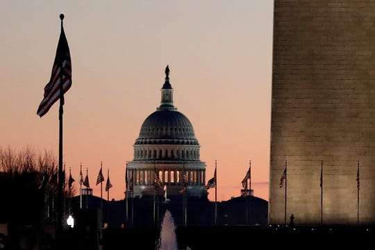 The U.S. Capitol building, center, and part of the Washington Monument, right, are seen at sunrise, Wednesday, Dec. 18, 2019, on Capitol Hill in Washington.