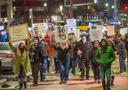 More than one hundred a pro-impeachment activists march along Fort Street in downtown Detroit on Tuesday night, on the eve of the U.S. House of Representatives' formal vote on impeachment against President Donald Trump.