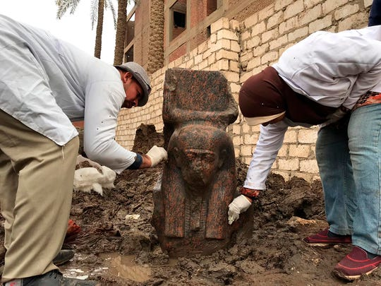 In this Wednesday, Dec. 11, 2019, photo released by Egyptian Ministry of Antiquities, archaeology workers clean a small pink granite statue of Ramses II, near the ancient pyramids of Giza, Egypt.