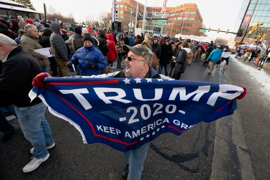 Robert Nicklay, of Detroit, chants in favor of President Trump to people waiting in line for a rally for the president at Kellogg Arena, in Battle Creek, December 18, 2019.