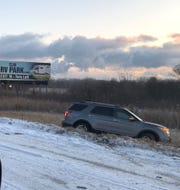 A damaged car sits in a ditch on the side of I-75 near exit 11 in Monroe County, where traffic was stopped for hours due to multiple crashes.