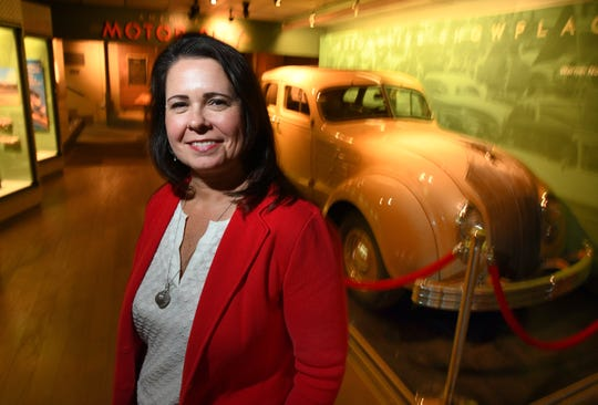 President and CEO Elana Rugh of the Detroit Historical Society stands beside the Automotive Showcase display at the Detroit Historical Museum.