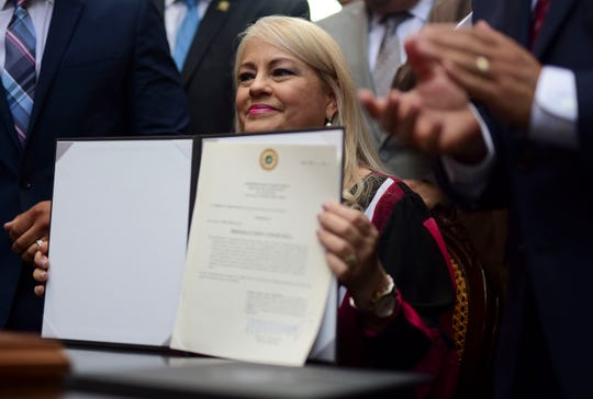 Governor Wanda Vazquez shows the bill she signed into law in favor of cockfighting, despite a federal ban that goes into effect this week, in San Juan, Puerto Rico, Wednesday, Dec. 18, 2019.