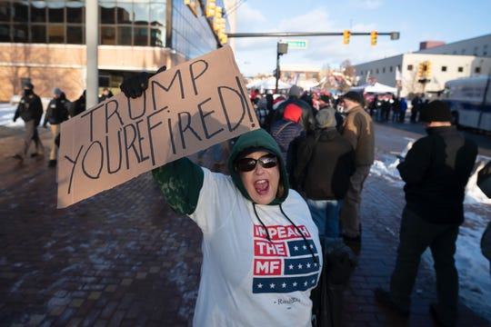 Linda Pascoe, of Battle Creek, a lone protestor in favor of impeachment yells at Trump supporters waiting in line for a rally for President Donald Trump.