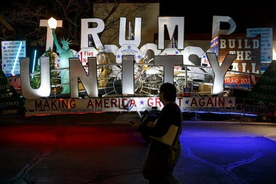 A supporter walks by a float decorated with slogans and President Trump memorabilia in Sterling Heights.