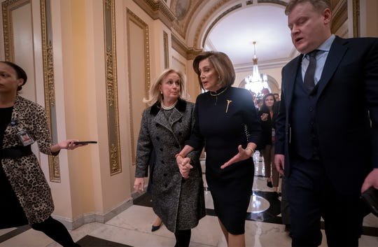 Speaker of the House Nancy Pelosi, D-Calif., holds hands with Rep. Debbie Dingell, D-Mich., as they walk to the chamber where the Democratic-controlled House of Representatives begins a day of debate on the impeachments charges.