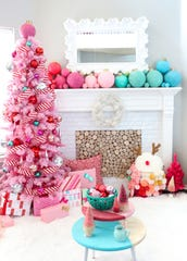 Kara Whitten fell in love with a pink-flocked tree and teamed it with red-and-white candy-striped ribbon, with supersized ornaments in pinks and aqua for her mantel. She designed the wrapping paper for the packages as well as the color-blocked tables, the reindeer and small trees.