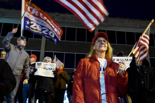 Mary McKannan stands out in the cold with other community members during an anti-impeachment rally outside of Evansville's Federal Building, Tuesday evening, Dec. 17, 2019. The group gathered to show support for President Donald Trump after a pro-impeachment rally was held in the same location earlier that day.