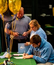 Cayden Baker signs paperwork with his parents by his side. Its National Signing Day and three Fort Myers athletes signed their letters to announce where they will play in College. Alaina Johnston,  Southeastern University to play golf, John Coleus, will play Football at Toledo, and Cayden Baker, will play Football at North Carolina.