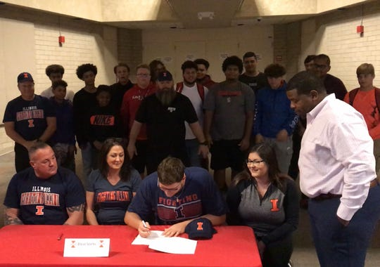 North Fort Myers offensive lineman Blaise Sparks signs to play at Illinois surrounded by his family, Red Knight head coach Dwayne Mack and his teammates Wednesday morning.