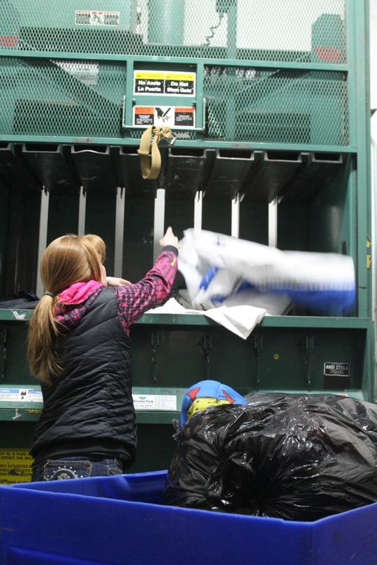 Amber Pearson loads unsellable clothing into the Rescue Mission Thrift Store's compactor. Nearly all of the cloth's are sold to third party vendors.
