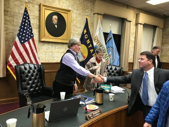 City Manager Greg Doyon shakes hands with outgoing Commissioner Bill Bronson after Bronson's final meeting Tuesday. Commissioner Mary Sheehy Moe sang a tribute to to Bronson during the meeting.