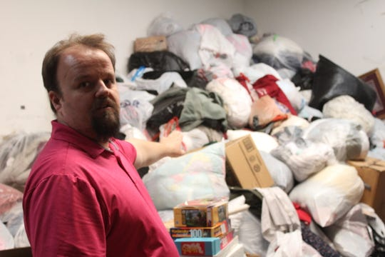 "Rescue Mission Thrift Store manger Matt Bessette stands before a mound of donated clothing in the store's receiving room. ""This is a comparatively small pile,"" Bessette observed."
