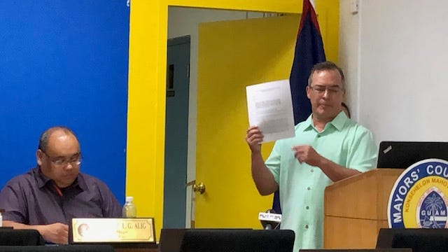 Sen. Jim Moylan raises a copy of a draft bill that he says will address vacancies in the offices of the mayor and vice mayor, as well as clarify the voting process for the Mayors' Council of Guam, during the mayors' Dec. 18, 2019 meeting.