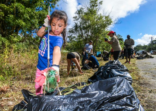 Olivia Cruz, 4, pitches in to do her part as she, her family members, service members of Andersen Air Force Base's 36th Security Forces Squadron and other volunteers collect trash and other illegally dumped items along Chalan Ramirez in Yigo, during a cleanup organized by Sen. Joe San Agustin, on Wednesday, Dec. 18, 2019.