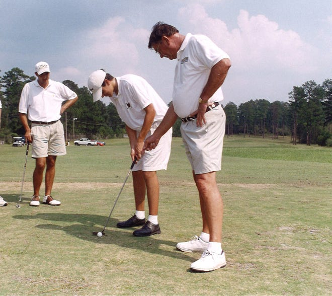 Golf coach Sam Hall works with a student.