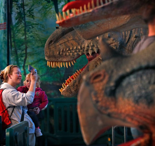 Jessica Pierce, left, holds her daughter Kiya Phillips and takes photos of her other daughter and giant dinosaurs at Jurassic Quest dinosaur event, Sunday, Oct. 6, 2019, at the Indiana State Fairgrounds.  Realistic, true-to-life dinosaurs from the Cretaceous, Jurassic, and Triassic periods, are replicated in the exhibit.  These dinosaurs were for riding.