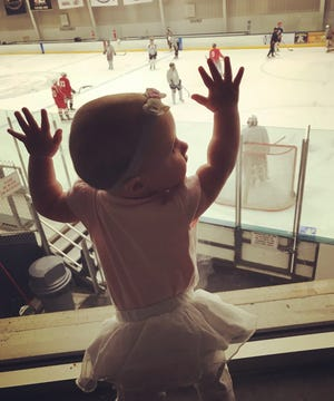 Chloe Wiegand banging on the glass at a hockey game