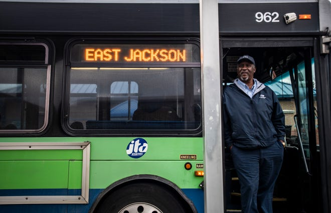 Tony Neely, 60, stands at the door of his Jackson Transit Authority bus on December 17, 2019 in Jackson, Tenn.