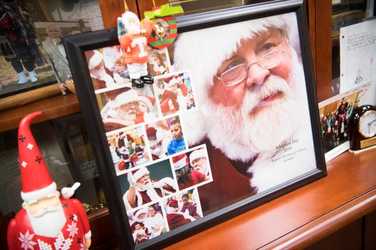Photos are seen of Blount County Mayor Ed Mitchell, dressed as Santa, in his office in Maryville, Tuesday, Dec. 3, 2019.  Mitchell has played Santa for over a decade.