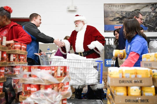 At left Jason Tipton greets Blount County Mayor Ed Mitchell, dressed as Santa, at the Empty Pantry Fund Thursday, Dec. 12, 2019.
