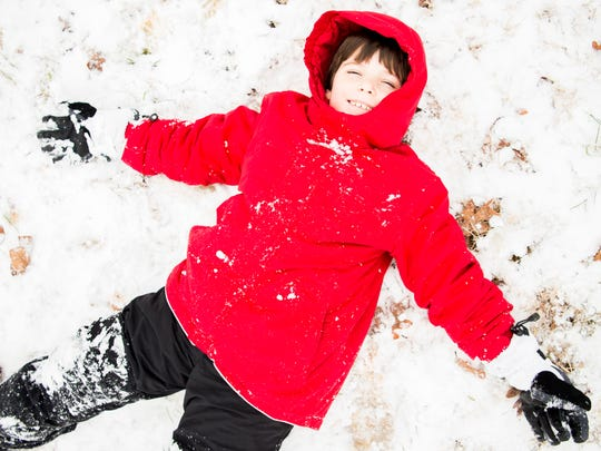 Mack Patterson happily lays in the snow after sledding at Lakeshore Park in Knoxville on Tuesday, Jan. 29, 2019.