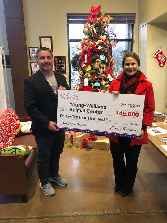 Eric Barton presents a check for $45K to Janet Testerman of Young-Williams Animal Center on Tuesday, Dec. 17, 2019.