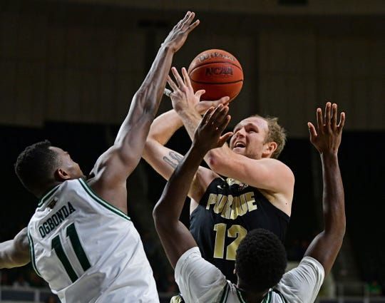 Purdue forward Evan Boudreaux (12) goes to the basket against Ohio forward Slyvester Ogbonda (11) and guard Lunden McDay (15) during the second half of an NCAA college basketball game, Tuesday, Dec. 17, 2019, in Athens, Ohio. Purdue won 69-51. (AP Photo/David Dermer)