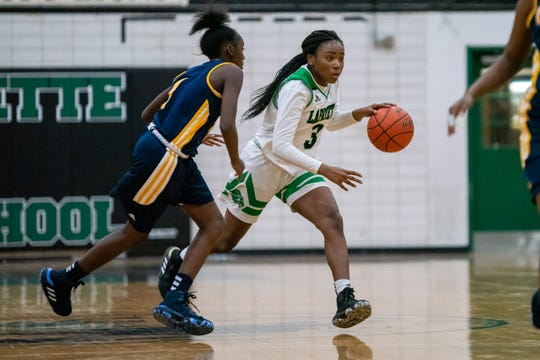 Lafayette High's Chrysta Narcisse dribbles the ball during the play as the Lafayette High Lady Lions take on the Carencro High Lady Bears on Tuesday, Dec. 17, 2019.